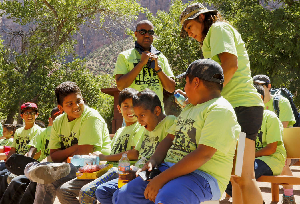Maria Gonzalez, center, sprays sunscreen on the neck of Brian Cruz, 10, before their hikes at Zion National Park, Saturday, June 10, 2017. One hundred fifty children from Las Vegas visited the par ...