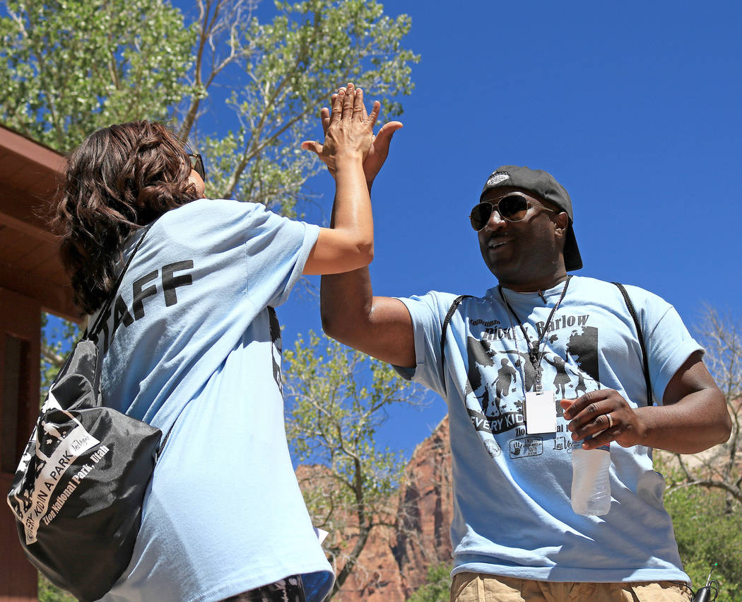 "Tva Parks, left, CEO and president of Connect Central Corporation, and Las Vegas City Councilman Ricki Barlow high-five their success at making the ""1 Million African American Youth In A Park"" pro ..."