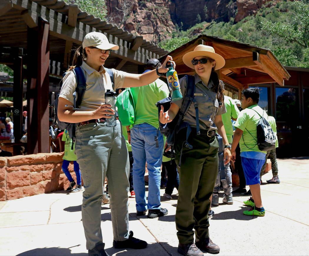 "Park Rangers Carmen Reese, left, and Lindsay Kaye take a water break in front of the lodge at Zion National Park during the ""1 Million African American Youth In A Park"", Saturday ..."