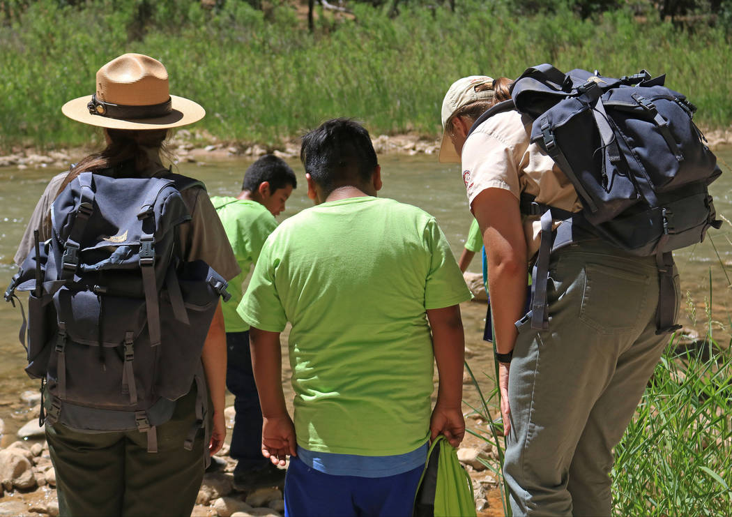 "Park Rangers Lindsay Kaye, left, and Carmen Reese, right, explain some of the biology that live in the river at Zion National Park during the ""1 Million African American Youth In A Park&a ..."
