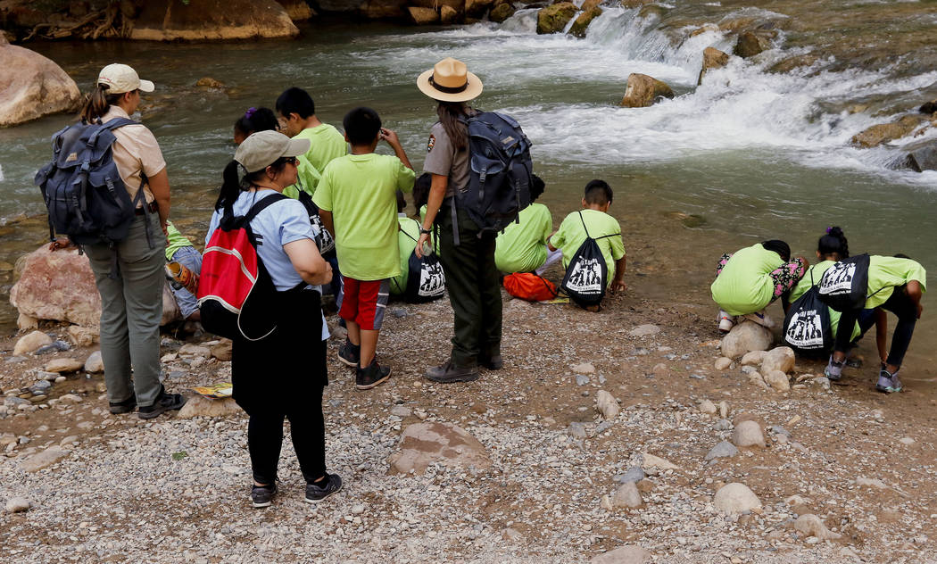 "Park Rangers Carmen Reese, left, and Lindsay Kaye, right, watch their group splash in the Virgin River at Zion National Park during the ""1 Million African American Youth In A Park&quo ..."