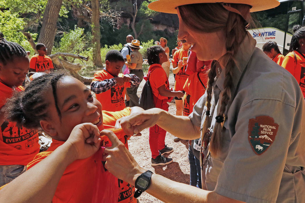 "Faith Francis, 10, left, gets help from Park Ranger Gustava Hoskins with pinning her Junior Ranger badge on her shirt at Zion National Park during the ""1 Million African American Youth In ..."
