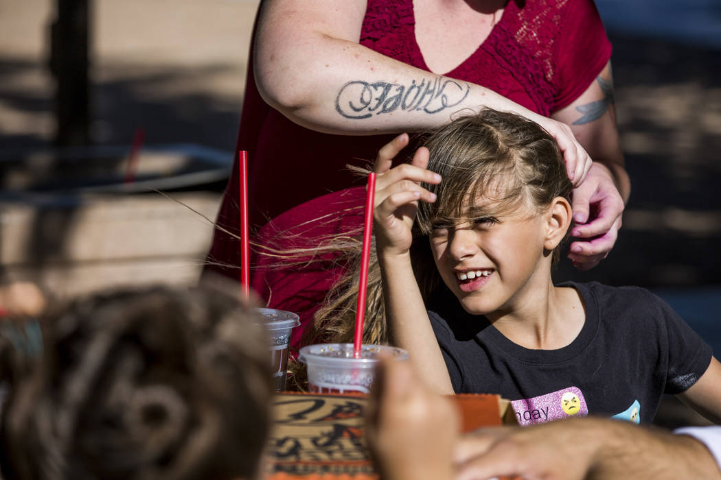Shendra Paprick attempts to fix eight-year-old Amari Hernandez's hair as the winds blows while she spends time with family and friends at Lorenzi Park on Sunday, June 11, 2017.  Patrick Connolly L ...