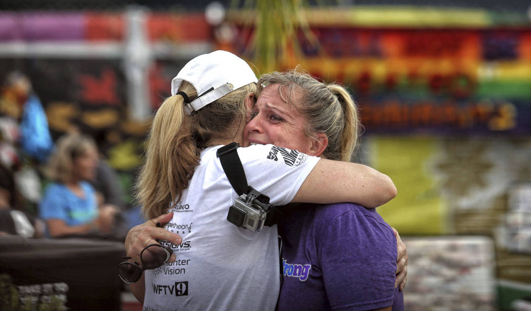 Runners Randa Black, left, and Elizabeth Anne-Noles cry after stopping in front of the Pulse nightclub during the CommUNITYRainbowRun 4.9K road race, Saturday, June 10, 2017, in Orlando, Fla. (Joe ...