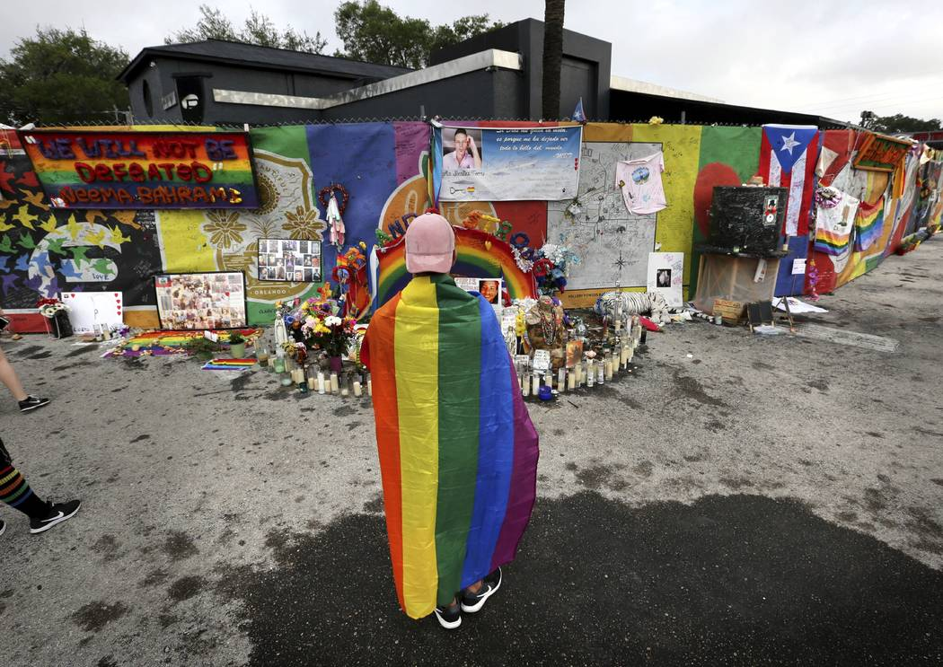 A runner wearing a gay pride rainbow flag pauses in front of the Pulse nightclub during the CommUNITYRainbowRun 4.9K road race, Saturday, June 10, 2017, in Orlando, Fla. The race is one of many ev ...