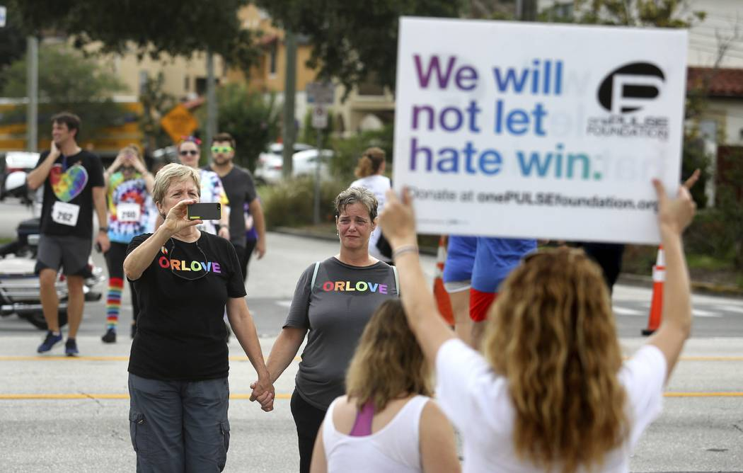 Pulse nightclub owner Barbara Poma holds up a sign for runners passing her club during the CommUNITYRainbowRun 4.9K road race, Saturday, June 10, 2017, in Orlando, Fla. (Joe Burbank/Orlando Sentin ...