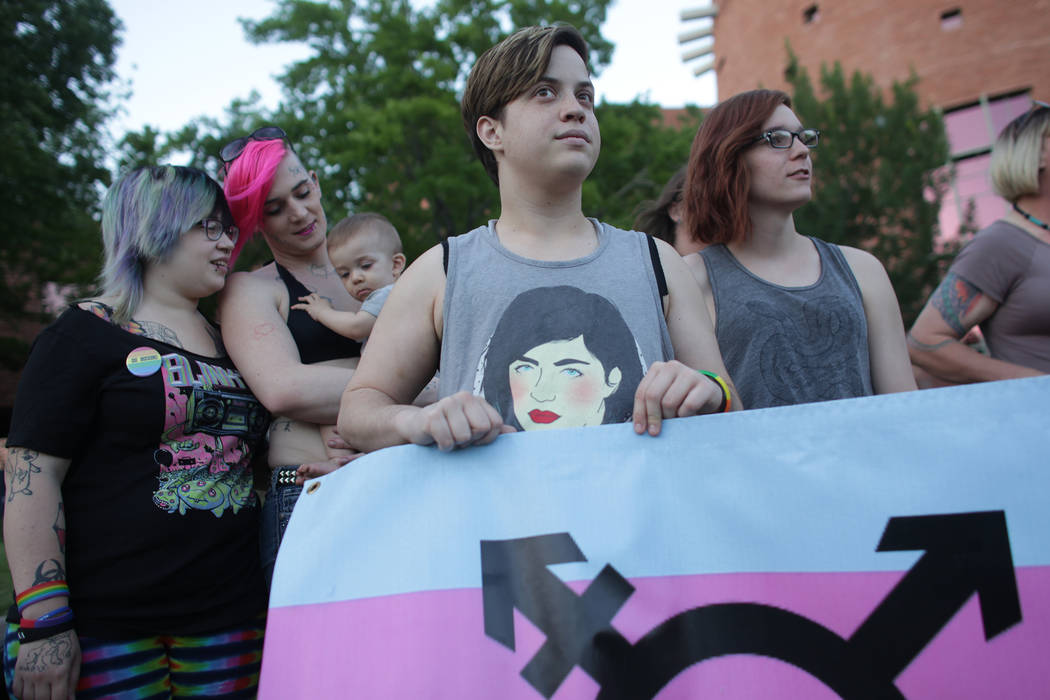 Danielle Anderson, from left, Rebel Rae, holding their son Dani Brown, Lyndon Rohde, and Zoey Henderson stand with a trans pride poster on Sunday, June 11, 2017, at the Equality Rally for Unity an ...
