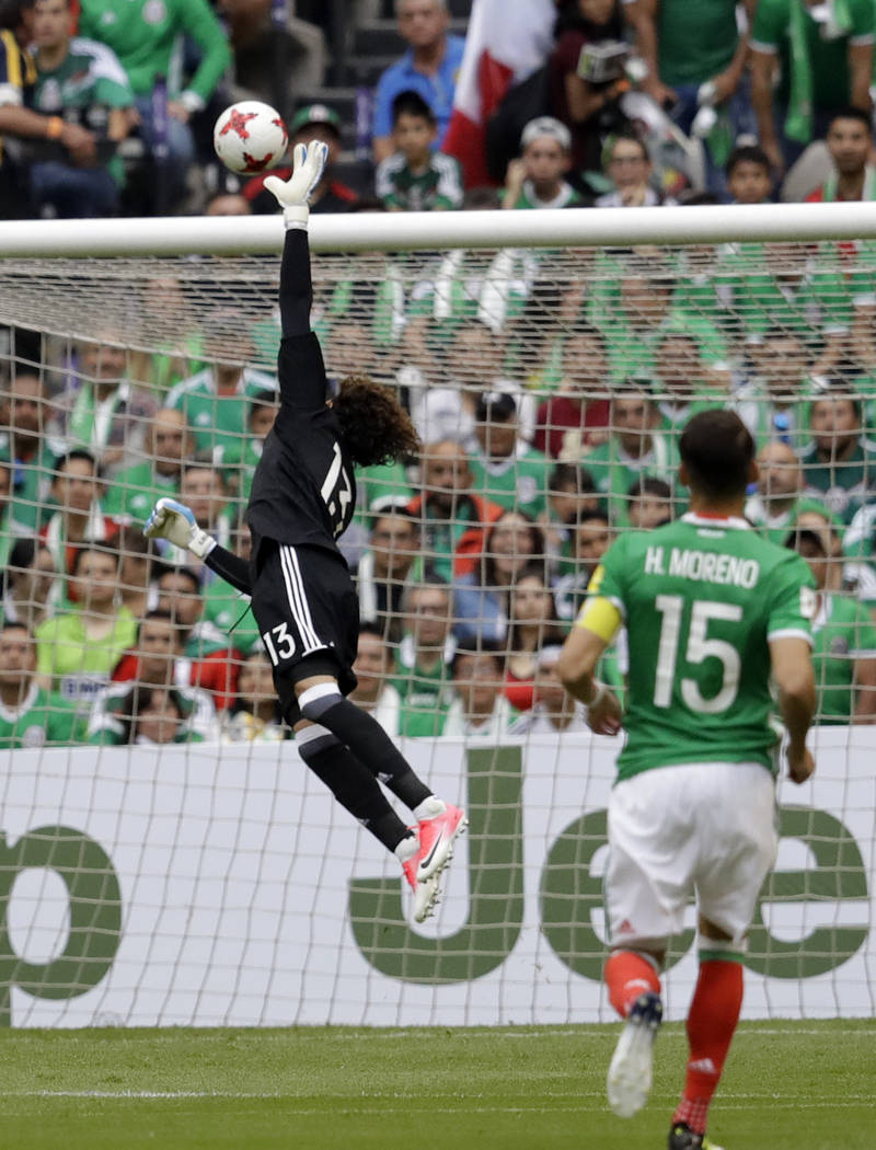 Mexico's goalkeeper Guillermo Ochoa tries to reach the ball as United States' Michael Bradley scores during their World Cup soccer qualifying match at Azteca Stadium in Mexico City, Sunday, June 1 ...