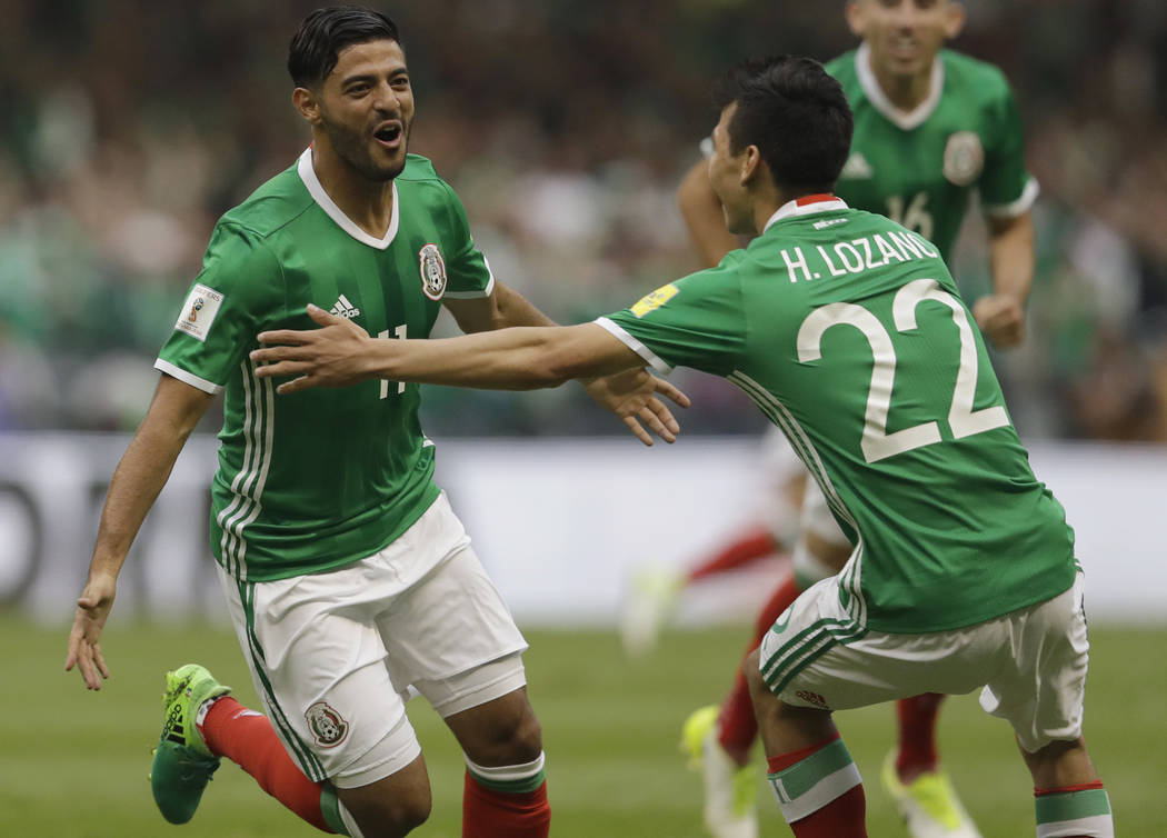 Mexico's Carlos Vela, left, celebrates with teammate Mexico's Hirving Lozano after scoring his team's first goal against the U.S. during their World Cup soccer qualifying match at Azteca Stadium i ...
