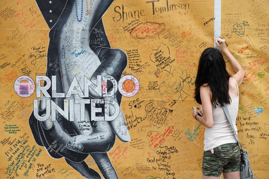 Mary Beth Nickerson signs the wall outside of Pulse Nightclub while visiting the memorial on the one year anniversary of the shooting in Orlando, Florida. (Scott Audette/Reuters)