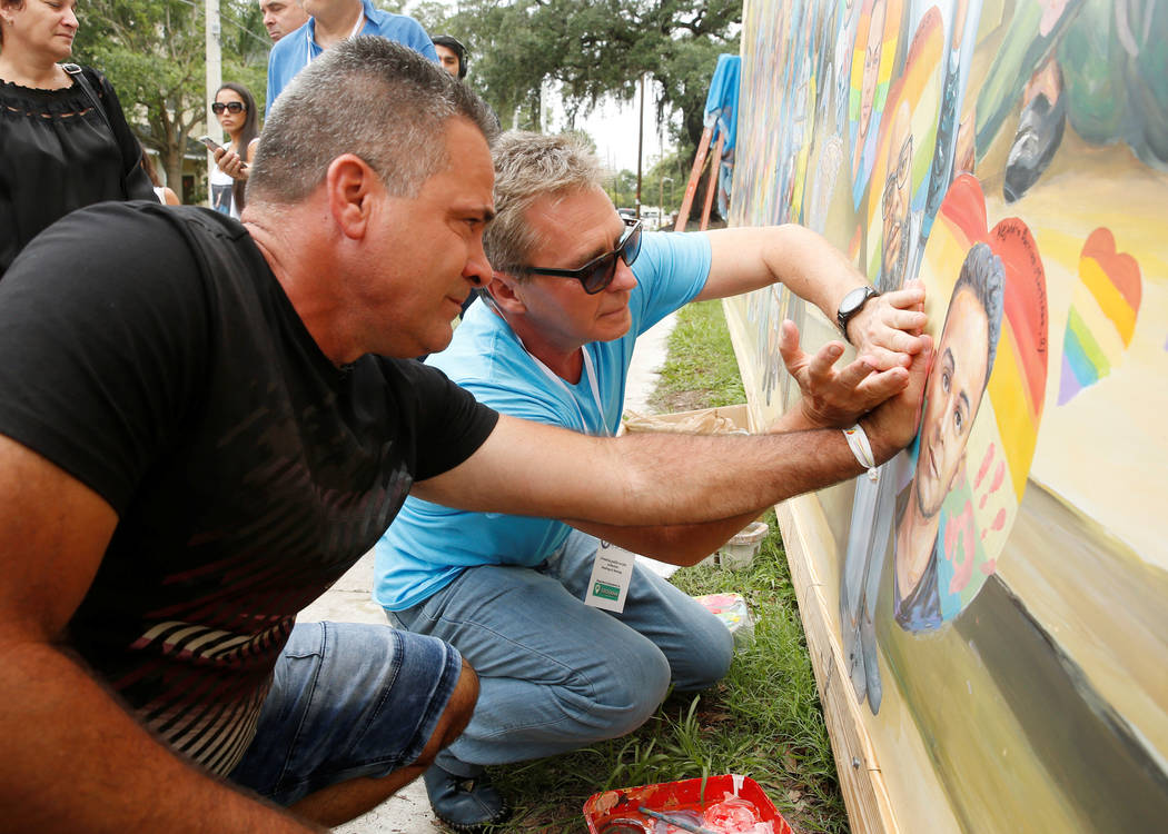 Saul Barrios (L) leaves his handprint on a mural that contains an image of his deceased son Alejandro Barrios Martinez, with the help of artist Yuri Karabash, at the memorial outside the Pulse Nig ...