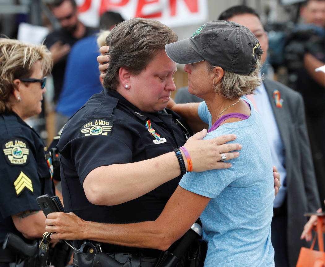 Orlando police department patrol officer Alison Clarke (L) is embraced by Christine Gogicos while visiting the memorial outside the Pulse Nightclub on the one-year anniversary of the shooting in O ...