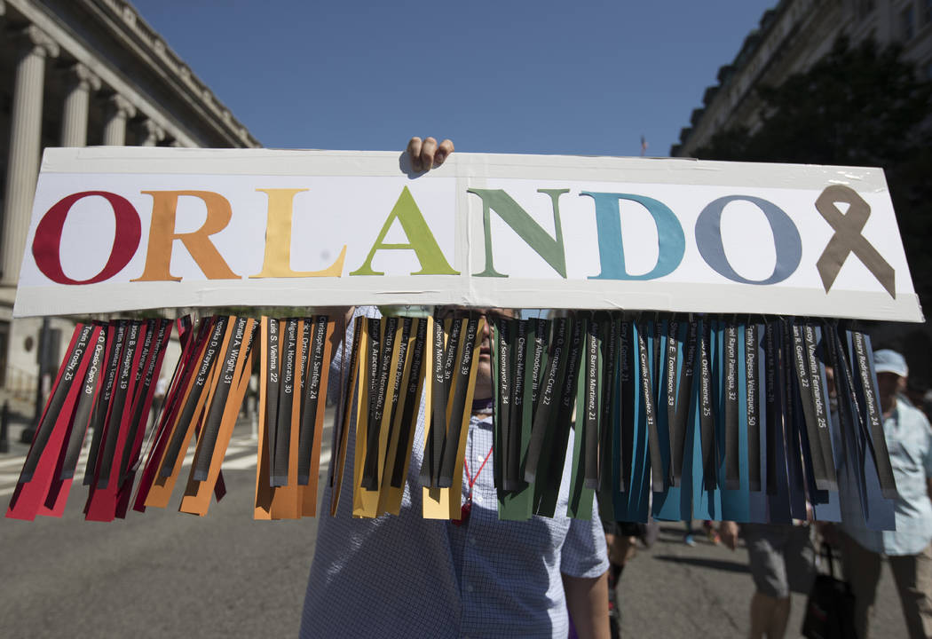 Gil Mendez, of San Francisco, holds a sign to honor the victims of the shooting at the Pulse Nightclub in Orlando, Fla., as he marches during the Equality March for Unity and Pride in Washington,  ...