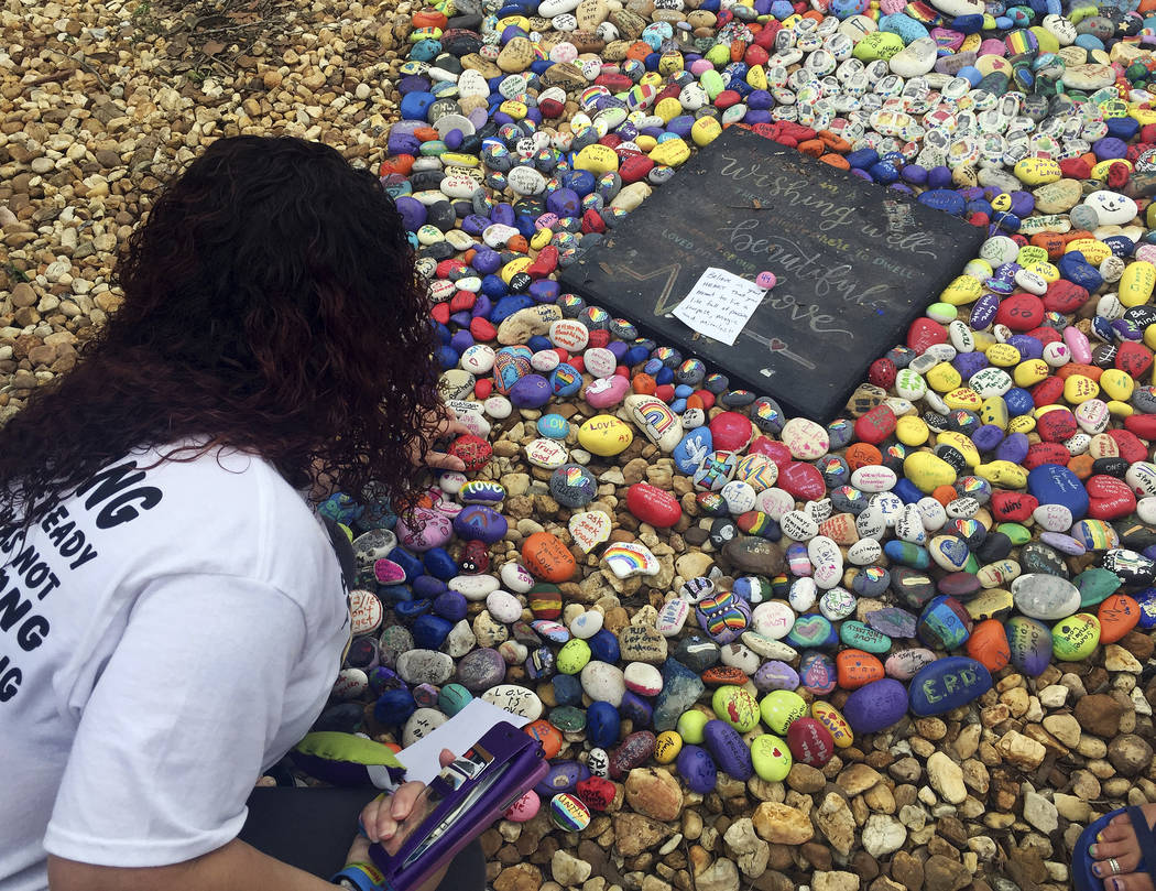 "Lizbeth DaVila looks over the rocks painted with inspirational messages at the ""Hugs Not Hate"" heart memorial outside the Pulse nightclub in Orlando, Fla., on Monday, June 12, 20 ..."