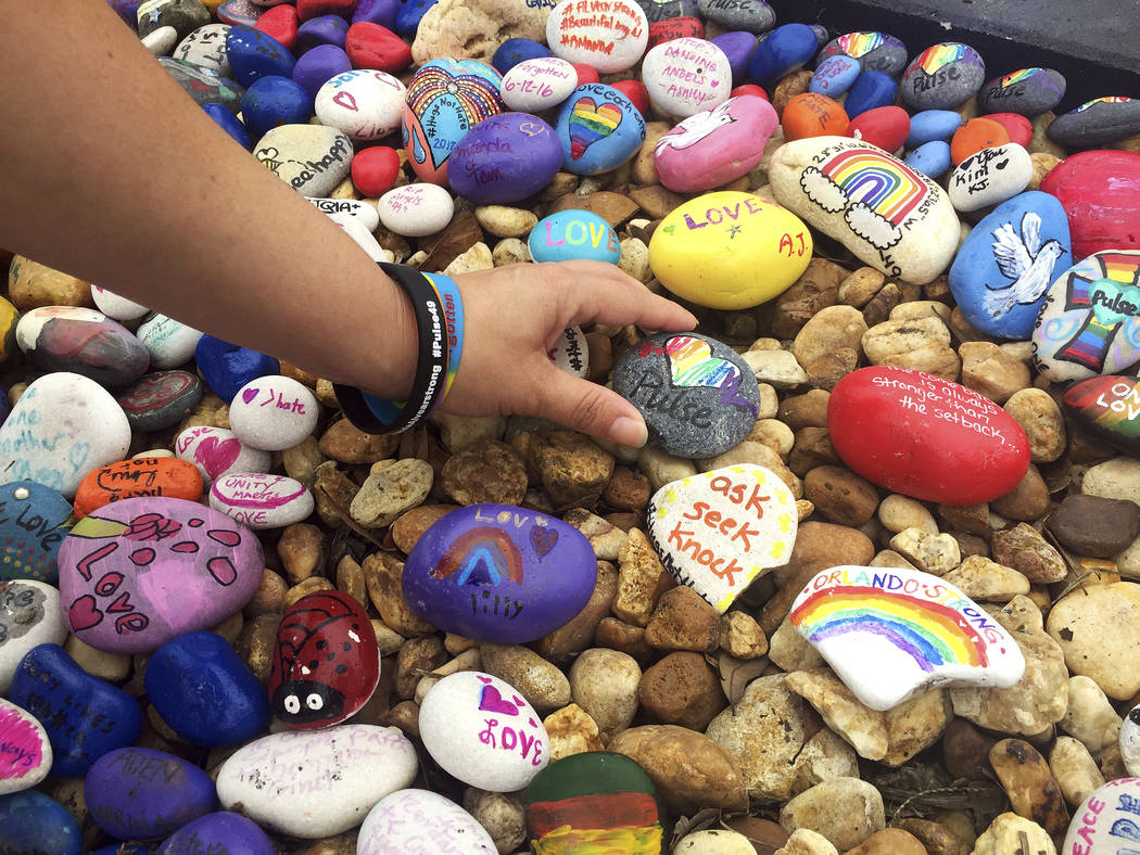 """Lizbeth DaVila touches a painted rock at the """"Hugs Not Hate"""" heart memorial outside Pulse nightclub in Orlando, Fla., Monday, June 12, 2017, in honor of the 49 people who lost th ..."""