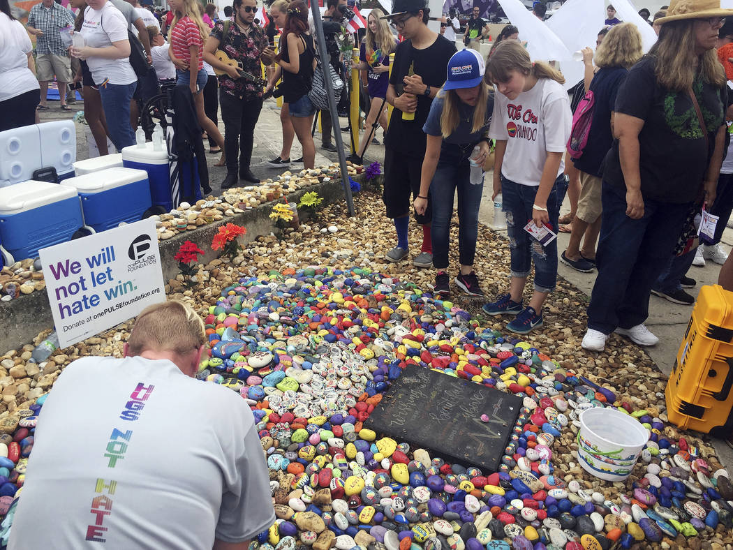 """People attend the """"Hugs Not Hate"""" heart memorial outside Pulse nightclub in Orlando, Fla., Monday, June 12, 2017, in honor of the 49 people who lost their lives in the shooting o ..."""