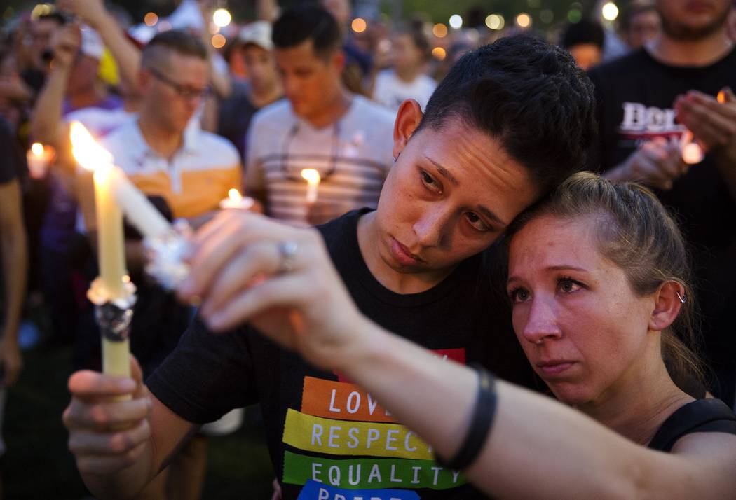 FILE - In this June 13, 2016 file photo, Jennifer, right, and Mary Ware light candles during a vigil downtown for the victims of a mass shooting at the Pulse nightclub in Orlando, Fla. Church bell ...