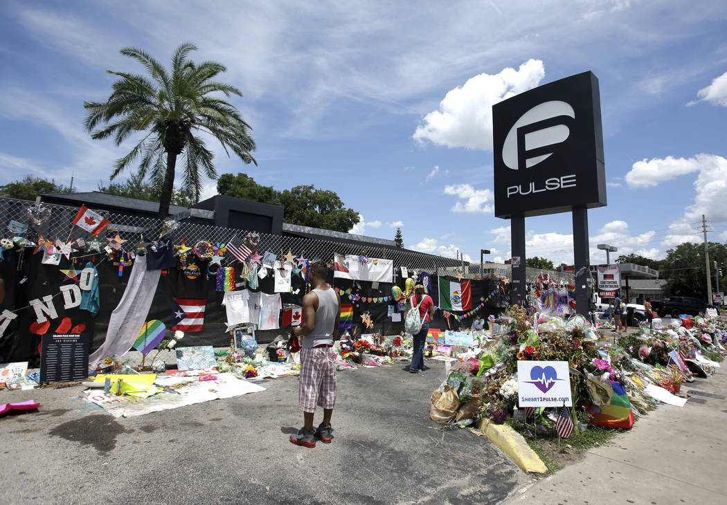 FILE - In this July 11, 2016, file photo, visitors gather at a makeshift memorial outside the Pulse nightclub in Orlando, Fla. Church bells will toll throughout the Orlando area as residents refle ...