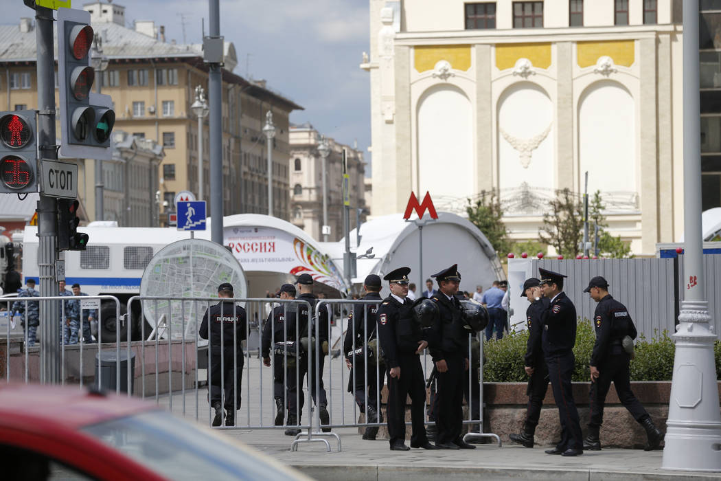 Russian police officers talk as they stand behind barricades in downtown Moscow, Monday, June 12, 2017. Russian opposition leader Alexei Navalny, aiming to repeat the nationwide protests that ratt ...