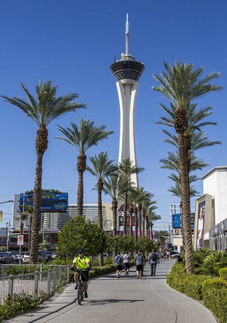 Pedestrians walk and a security guard bikes on South Las Vegas Boulevard near the Stratosphere on Monday, June 12, 2017. Golden Entertainment, operators of the PT's Pubs chain is acquiring a compa ...