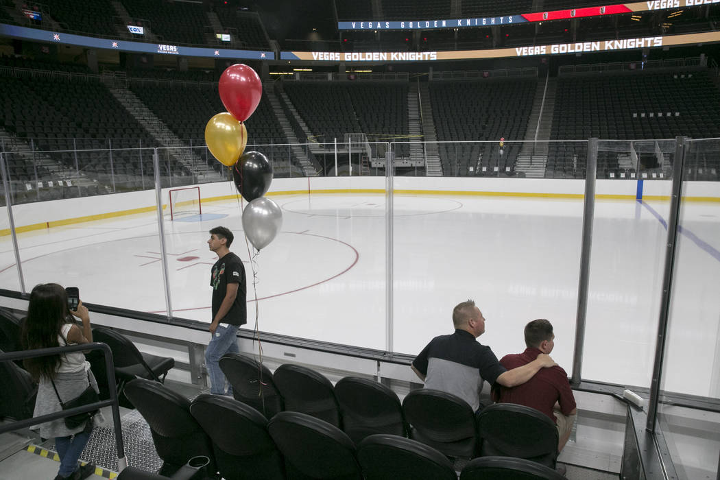 From left: Skye Mcdevitt of Northwest Vegas takes a selfie while Tom Oehler and his son Griffin Oehler, 16, both of Las Vegas, check out glass seats at the T-Mobile Arena in Las Vegas, Tuesday, Ju ...