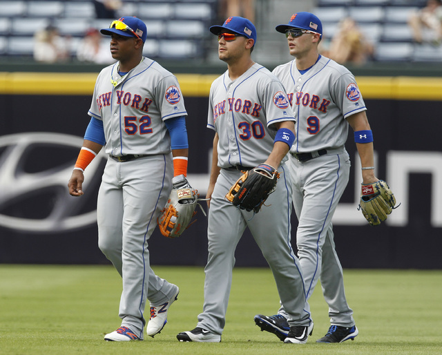New York Mets out fielders Yoenis Cespedes, left to right, Michael Conforto and Brandon Nimmo walk from the outfield after their win over the Atlanta Braves at a baseball game in Atlanta Sunday, S ...