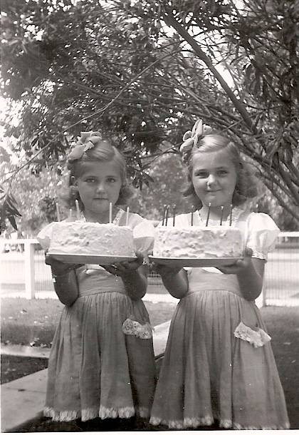 Carolyn and Madelyn Hardy hold up matching cakes while wearing matching dresses at their 7th birthday party in 1944.