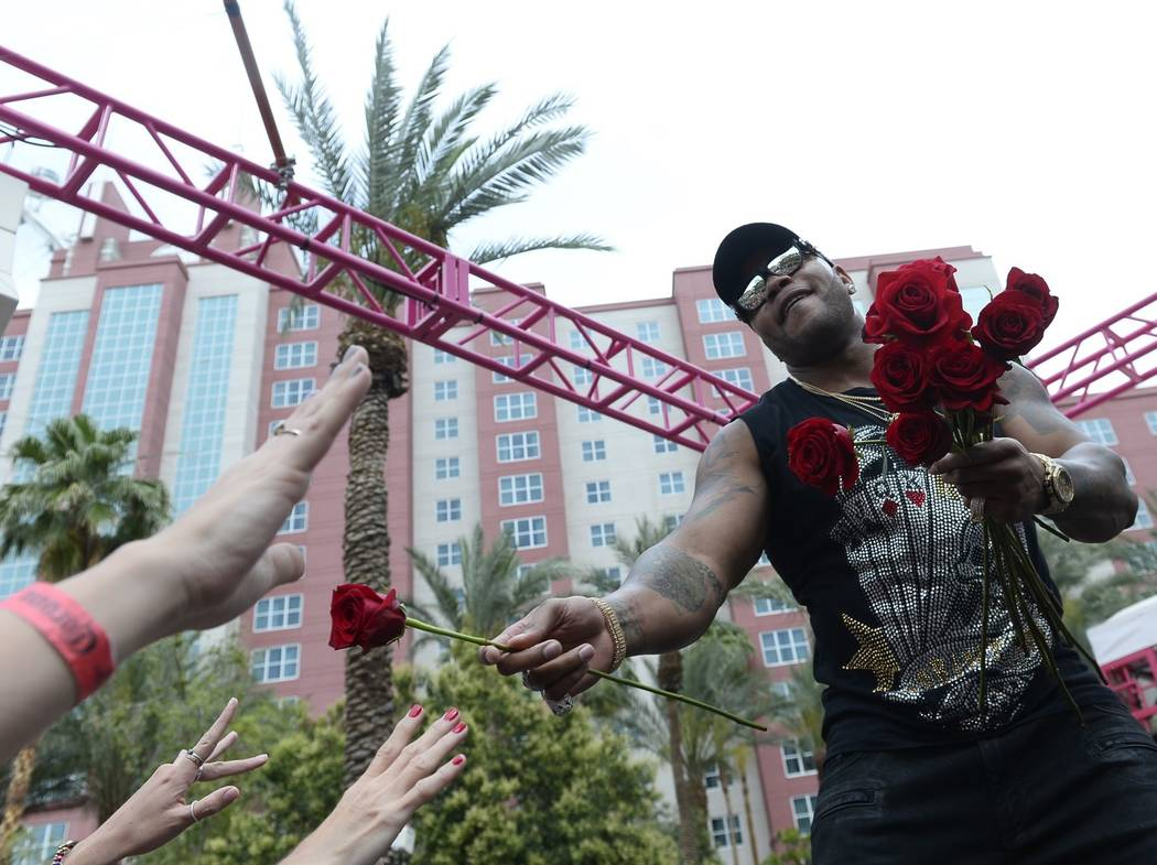 Recording artist Flo Rida hands out roses during his weekend performance at The Flamingo pool.  (Bryan Steffy)