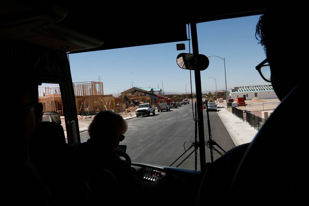 Attendees ride the bus during a motor coach tour of new neighborhoods in North Las Vegas, Wednesday, June 14, 2017. Attendees take a tour around the key residential and commercial development site ...