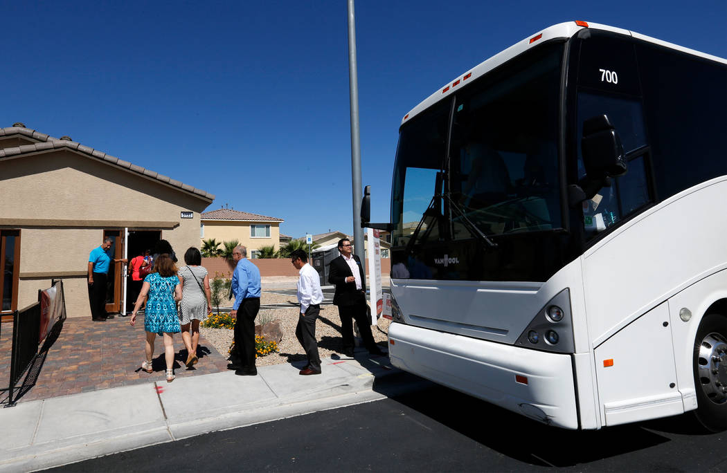 Attendees get off the bus during a motor coach tour of new neighborhoods in North Las Vegas, Wednesday, June 14, 2017, to see model houses by Beazer Homes at Falcon Ridge community. Attendees take ...