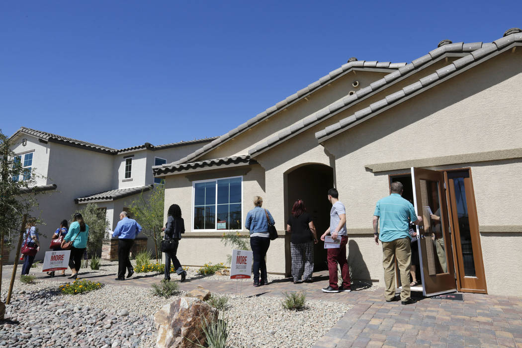 Attendees go to see model houses by Beazer Homes at Falcon Ridge community in North Las Vegas during a motor coach tour of new neighborhoods, Wednesday, June 14, 2017. Attendees take a tour around ...