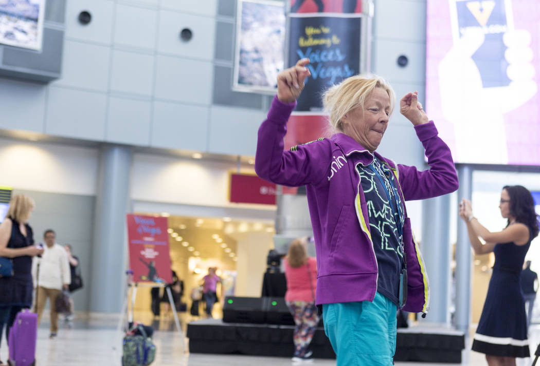 Tourist Regina Bauer dances as students who attend an after-school program at Enterprise Library, perform a DJ-ing set inside the D-Gate concourse at McCarran International Airport in Las Vegas, T ...