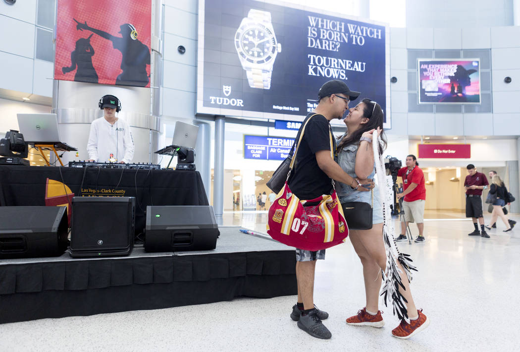 "Victor Arevalo, center, and Tiare Hernandez, right, embrace inside the D-Gate Concourse at McCarran International Airport in Las Vegas, Thursday, June 15, 2017, as Juan Arenas, ""DJ Juan,& ..."