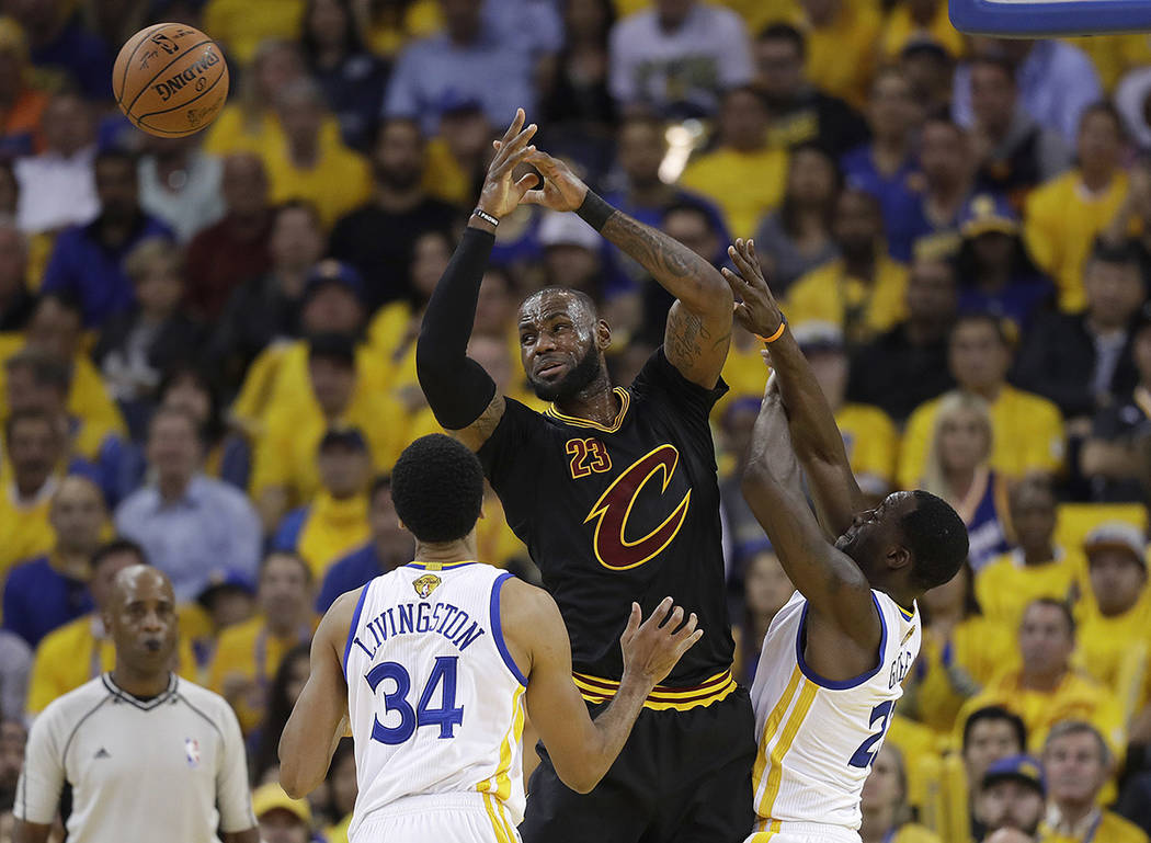 Cleveland Cavaliers forward LeBron James, center, loses the ball while guarded by Golden State Warriors guard Shaun Livingston (34) and forward Draymond Green during the first half of Game 5 of ba ...