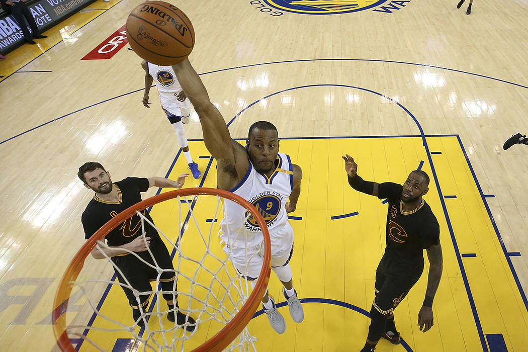 Golden State Warriors forward Andre Iguodala (9) dunks between Cleveland Cavaliers forward Kevin Love (0) and forward LeBron James (23) during the first half of Game 5 of basketball's NBA Finals i ...