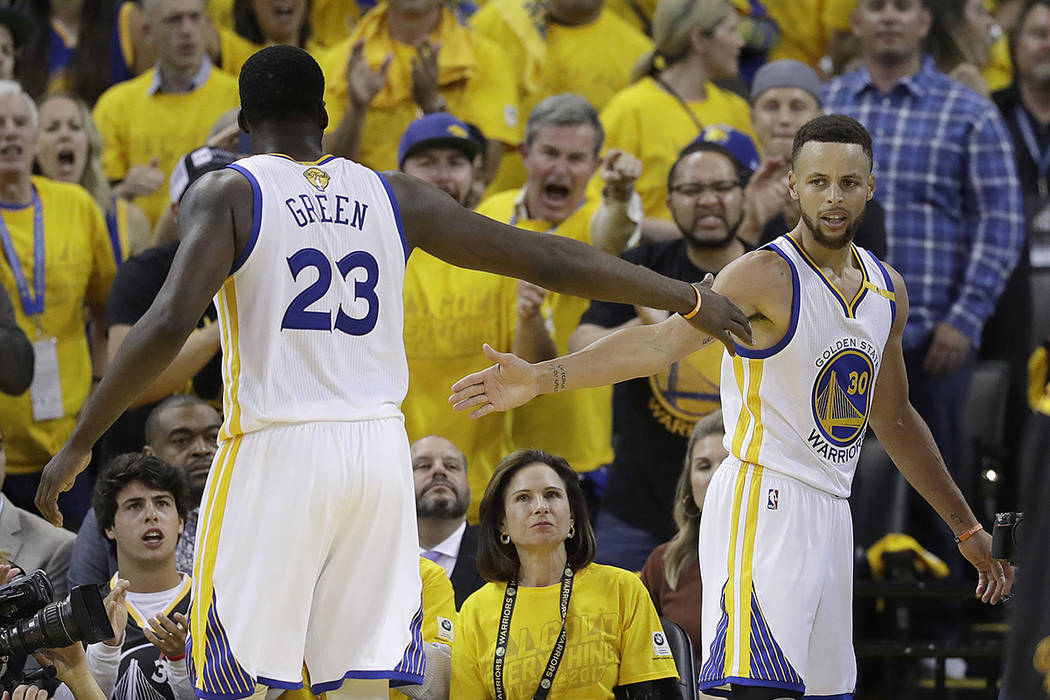 Golden State Warriors forward Draymond Green (23) and guard Stephen Curry (30) celebrate during the second half of Game 5 of basketball's NBA Finals against the Cleveland Cavaliers in Oakland, Cal ...