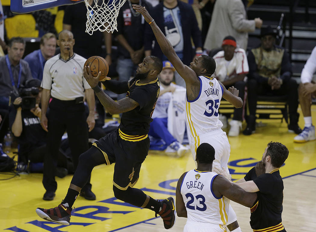Cleveland Cavaliers forward LeBron James, left, shoots against Golden State Warriors forward Kevin Durant (35) during the second half of Game 5 of basketball's NBA Finals in Oakland, Calif., Monda ...