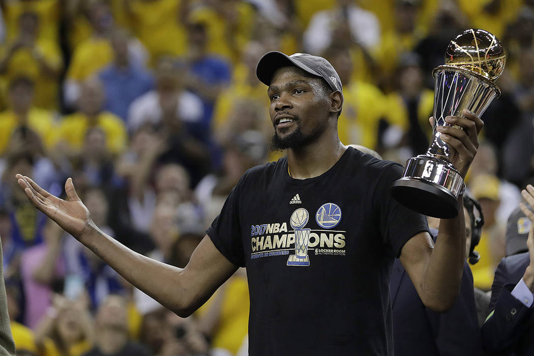 Golden State Warriors forward Kevin Durant gestures as he holds the Bill Russell NBA Finals Most Valuable Player Award after Game 5 of basketball's NBA Finals between the Warriors and the Clevelan ...