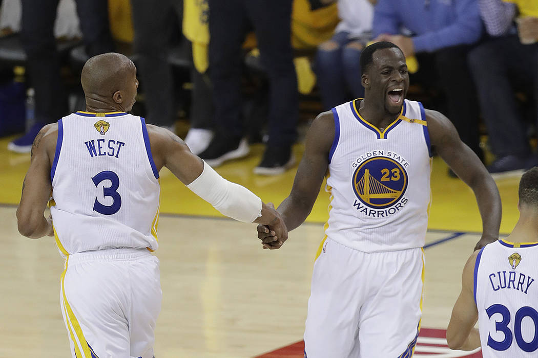 Golden State Warriors forward David West (3) celebrates with forward Draymond Green (23) during the first half of Game 5 of basketball's NBA Finals against the Cleveland Cavaliers in Oakland, Cali ...