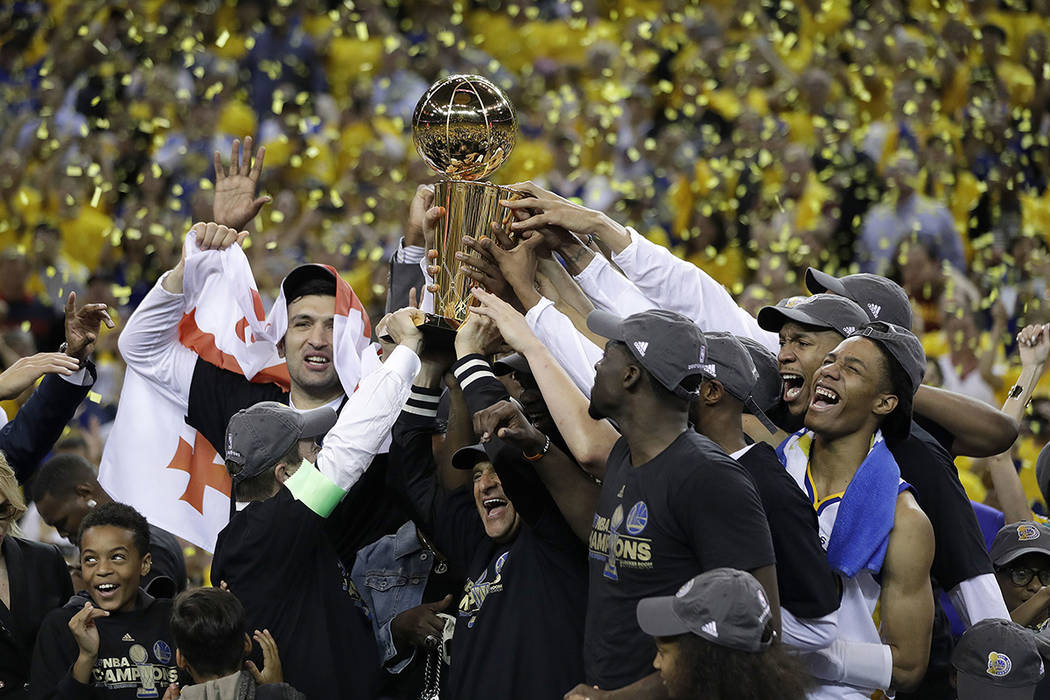 Golden State Warriors players, coaches and owners hold up the Larry O'Brien NBA Championship Trophy after Game 5 of basketball's NBA Finals between the Warriors and the Cleveland Cavaliers in Oakl ...