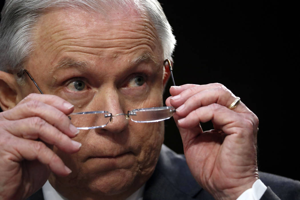 Attorney General Jeff Sessions removes his glasses as he speaks on Capitol Hill in Washington, Tuesday, June 13, 2017, while testifying before the Senate Intelligence Committee hearing about his r ...