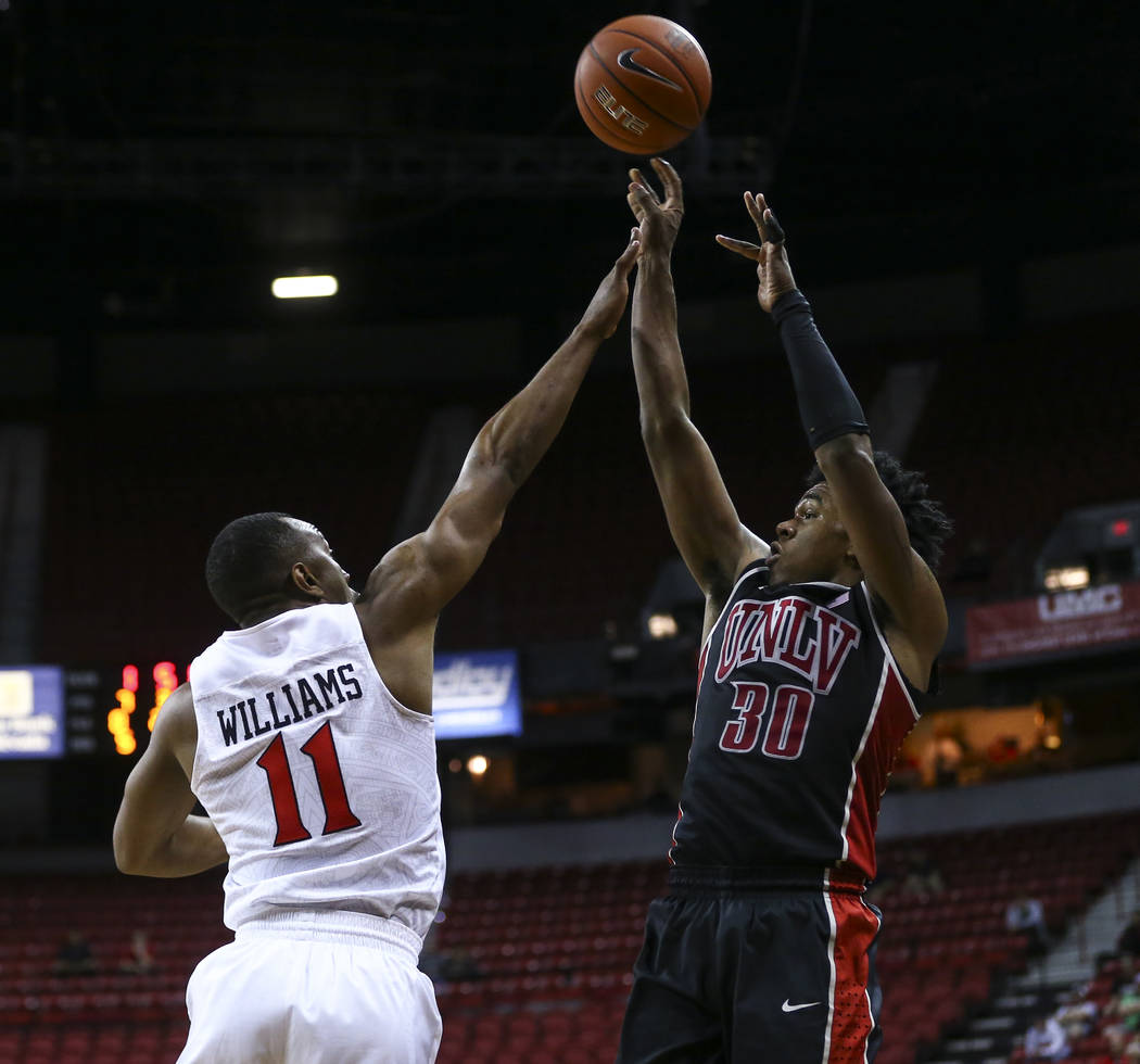 UNLV guard Jovan Mooring (30) shoots over San Diego State guard D'Erryl Williams (11) during a Mountain West Conference tournament basketball game at the Thomas & Mack Center in Las Vegas on W ...