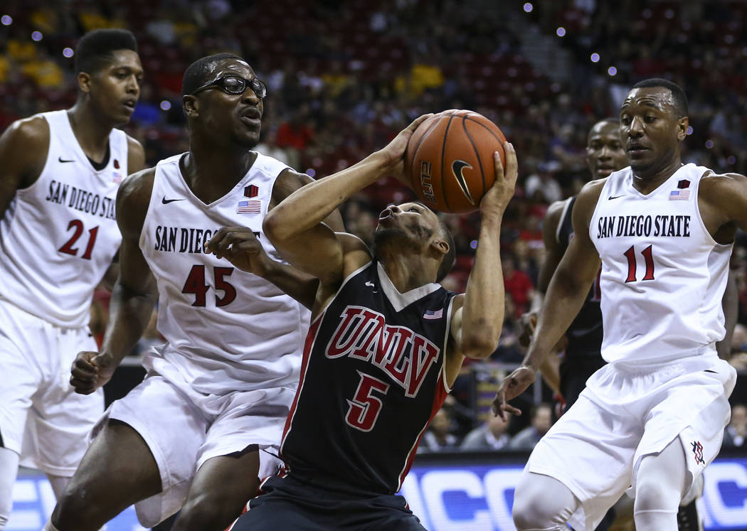 UNLV guard Jalen Poyser (5) drives to the basket against San Diego State center Valentine Izundu (45) during a Mountain West Conference tournament basketball game at the Thomas & Mack Center i ...