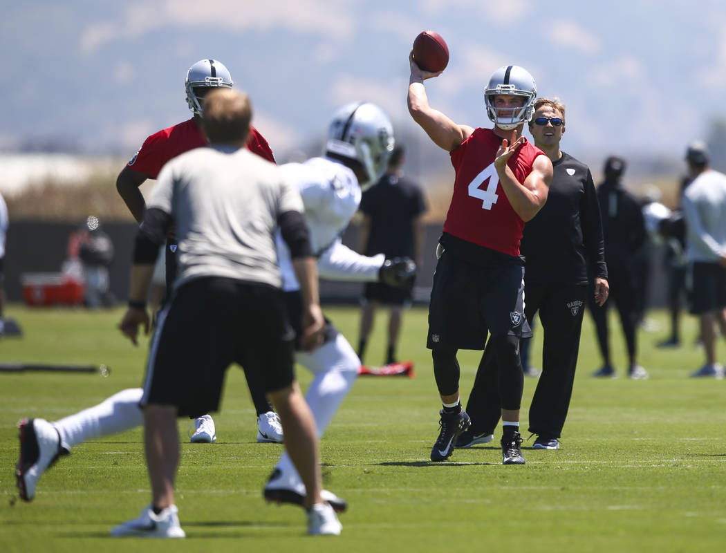 Oakland Raiders quarterback Derek Carr (4) throws a pass to wide receiver Michael Crabtree (15) during day one of a mini-camp at the Raiders headquarters and training facility in Alameda, Calif. o ...