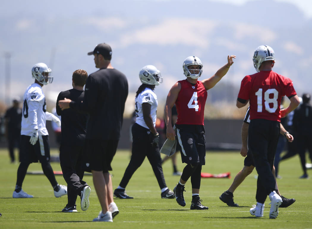 Oakland Raiders quarterback Derek Carr (4) motions to teammates during day one of a mini-camp at the Raiders headquarters and training facility in Alameda, Calif. on Tuesday, June 13, 2017. Chase  ...