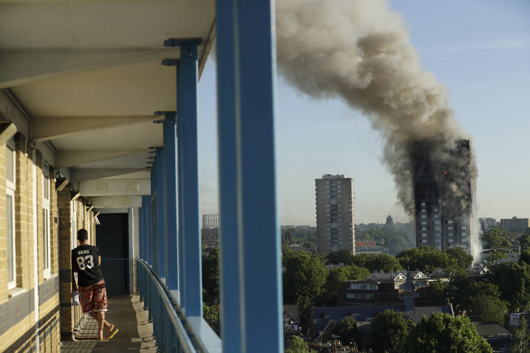 A resident in a nearby building watches smoke rise from a building on fire in London, Wednesday, June 14, 2017. A massive fire raced through the 27-story high-rise apartment building in west Londo ...