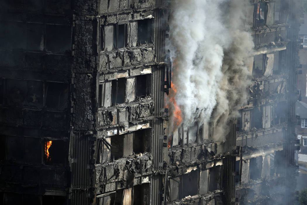 Parts of the building still burn hours after a deadly blaze at a high rise apartment block in London, Wednesday, June 14, 2017. Fire swept through a high-rise apartment building in west London ear ...