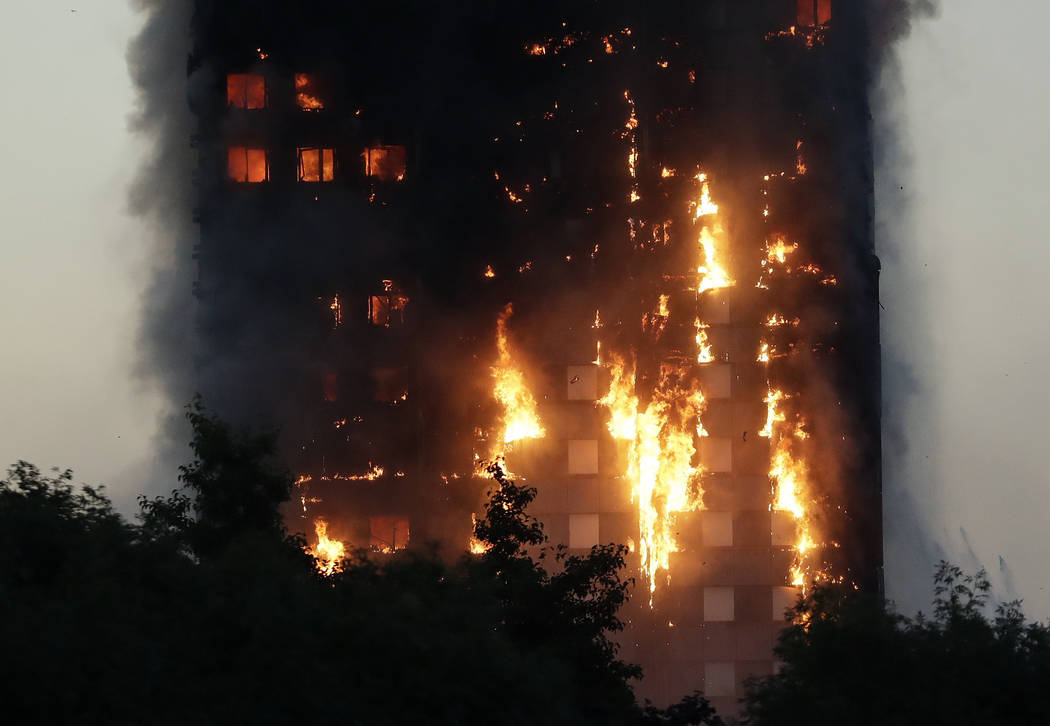 Smoke and flames rise from a building on fire in London, Wednesday, June 14, 2017. Metropolitan Police in London say they're continuing to evacuate people from a massive apartment fire in west Lon ...