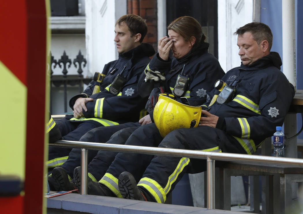 Firefighters wait to start their shift after a massive fire raged in a 27-floor high-rise apartment building in London, Wednesday, June 14, 2017. London's Metropolitan Police said a number of peop ...