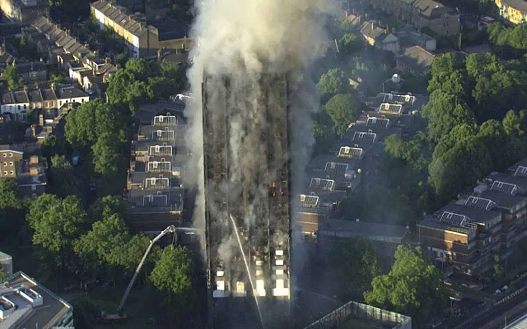 In this photo taken from aerial video, smoke rises from a high-rise apartment building on fire in London, Wednesday, June 14, 2017. A massive fire raced through the 27-story high-rise apartment bu ...